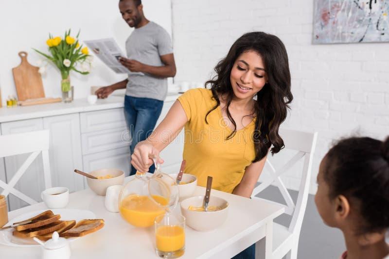 счастливая мать лить апельсиновый сок для дочери на завтраке пока газета чтения отца запачкала стоковое фото rf