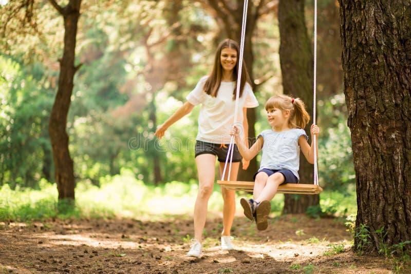 Счастливая мать нажимая смеясь дочь на качании стоковое фото