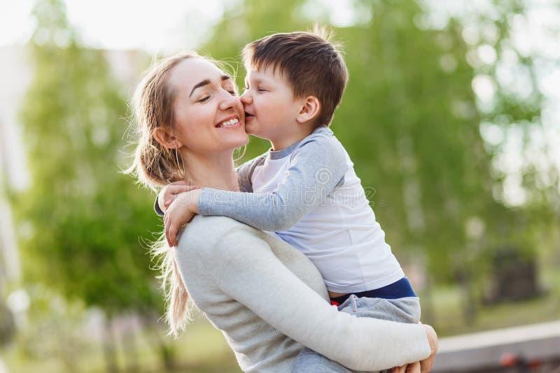 Счастливая мать обнимая ее маленького сына outdoors стоковые фотографии rf