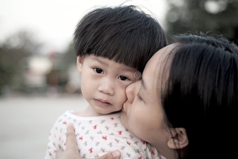 Счастливая мать обнимая и целуя ее сына стоковые изображения rf
