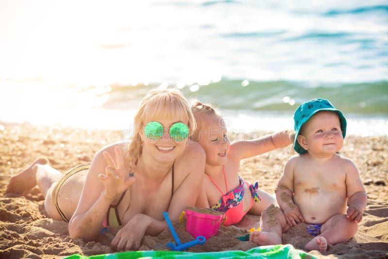 Счастливая мать отдыхая на море с ее дочерью стоковое фото rf
