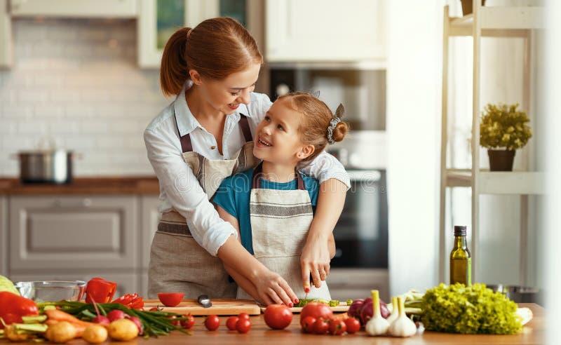 Счастливая мать семьи с девушкой ребенка подготавливая салат овоща стоковое изображение rf