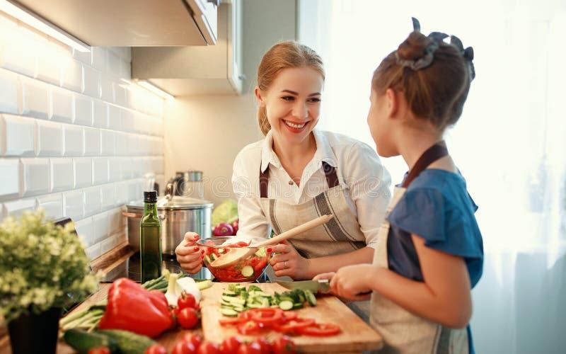 Счастливая мать семьи с девушкой ребенка подготавливая салат овоща стоковое фото rf
