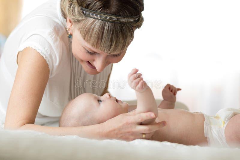 Счастливая мать смотря младенца в спальне стоковая фотография