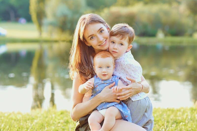 Счастливая мать с детьми в парке лета стоковое изображение