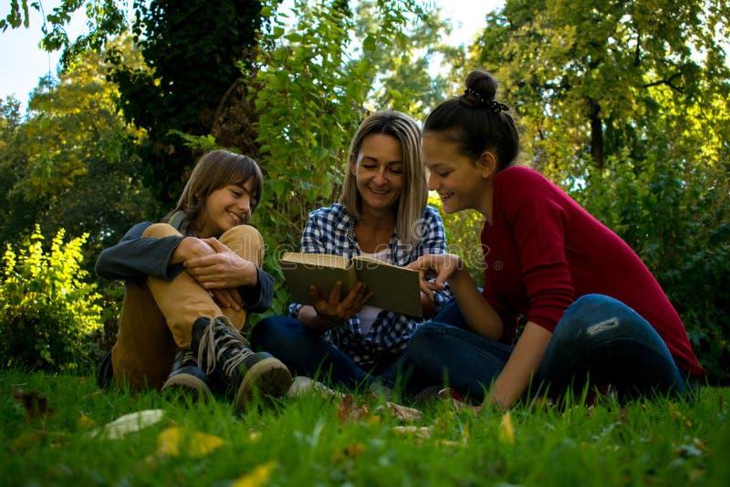 Счастливая мать читая книгу к ее подростковым детям в природе стоковое изображение rf