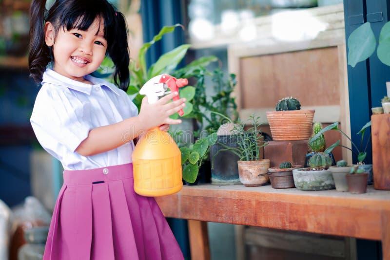 Счастливая милая азиатская девушка наслаждаясь с садовничая деятельностью, ребенок 3 лет старый в форме студента моча завод в стоковое изображение