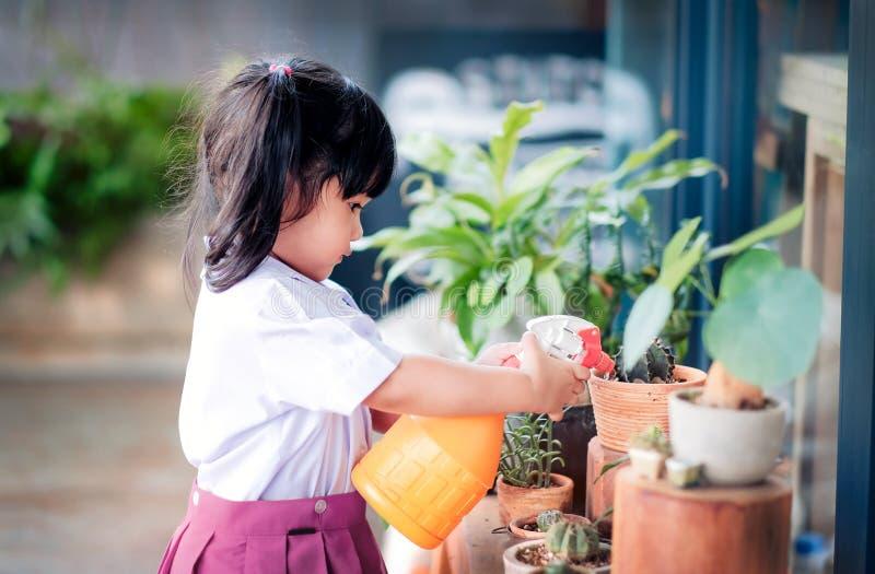 Счастливая милая азиатская девушка наслаждаясь с садовничая деятельностью, ребенок 3 лет старый в форме студента моча завод в стоковые изображения rf