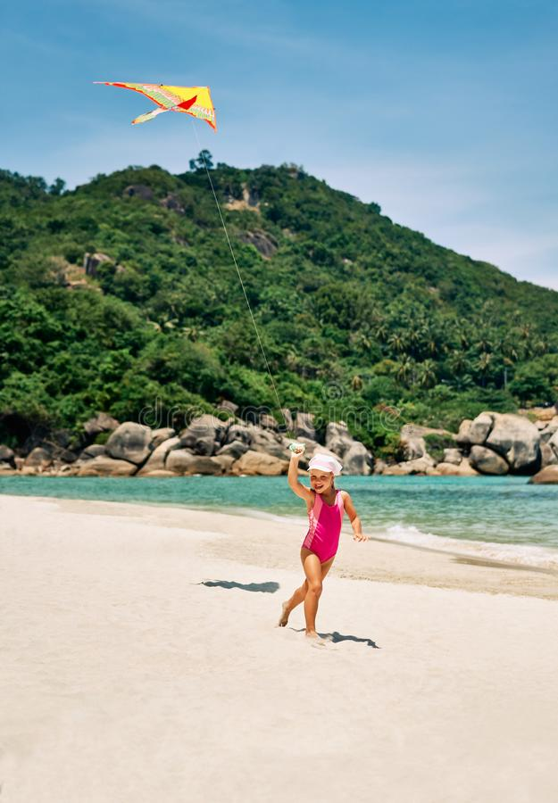 Счастливая милая девушка ребенка со змеем бежать на тропическом пляже летом стоковые изображения