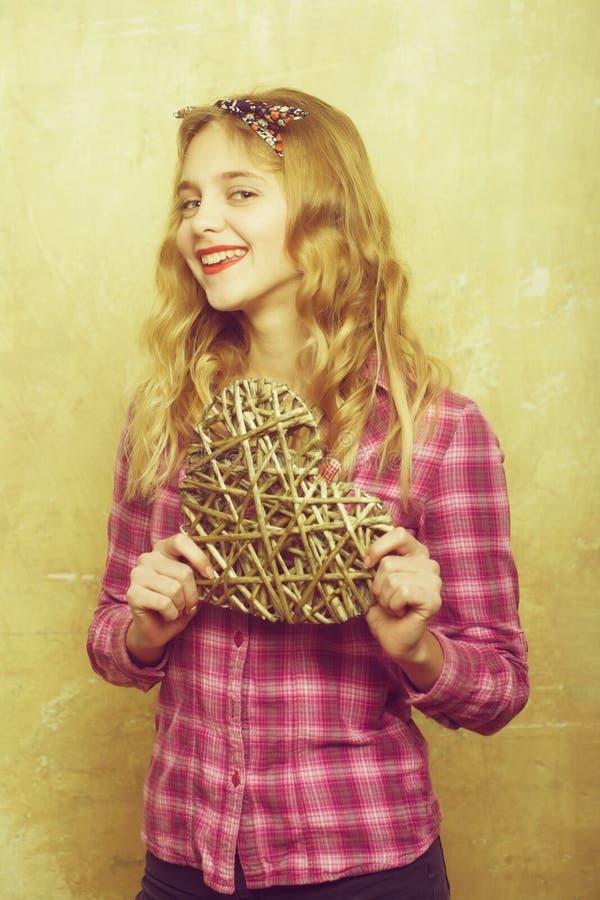 Счастливая милая девушка с плетеным сердцем на день Святого Валентина стоковые фотографии rf