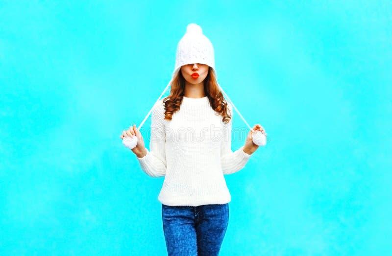 Счастливая милая женщина с красными губами делает поцелуй воздуха в связанной шляпе, свитере стоковые изображения rf