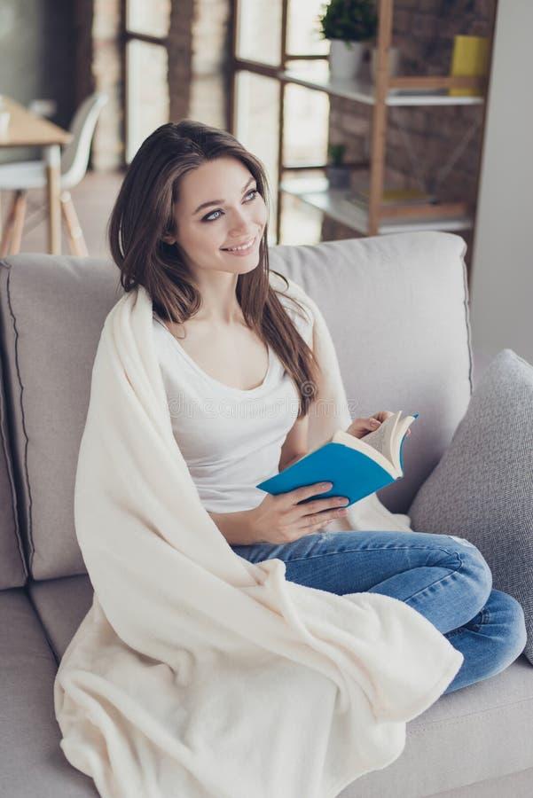 Счастливая милая книга чтения женщины на софе в выходные читая любимую книгу о влюбленности держа книгу в руках сидя на кресле стоковая фотография