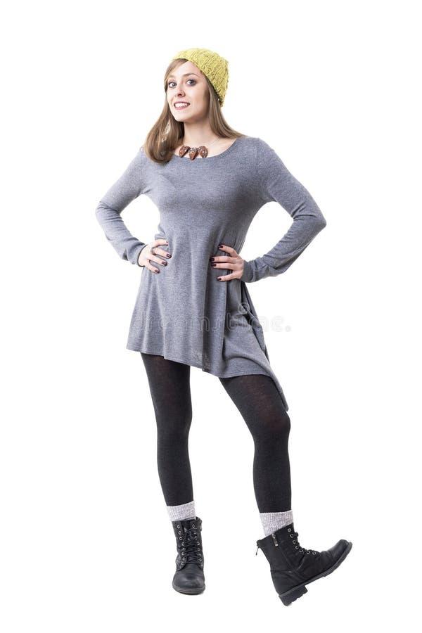 Счастливая милая любопытная молодая женщина в стильных одеждах осени с руками на бедрах стоковое изображение rf