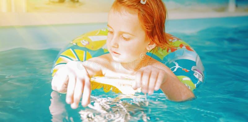 Счастливая милая маленькая девочка в бассейне Ребенок учит поплавать стоковое изображение rf