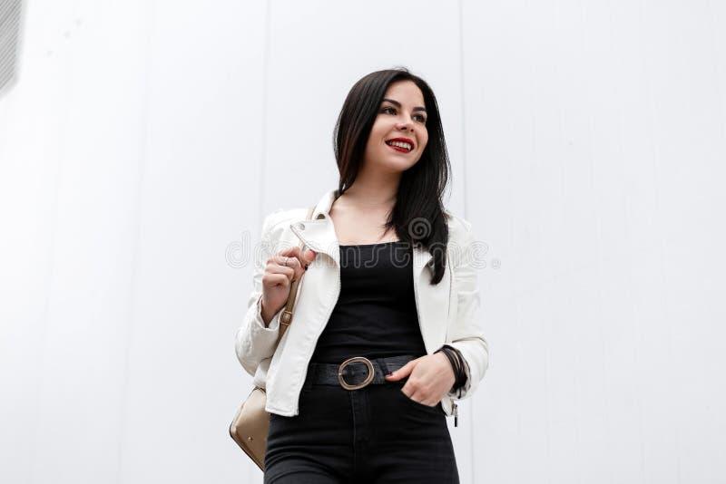 Счастливая милая молодая женщина с красными губами в винтажной белой кожаной куртке со стильным рюкзаком в черных джинсах стоит стоковые фото