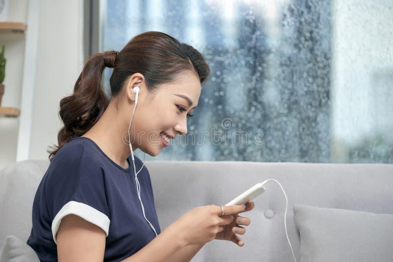 Счастливая молодая азиатская женщина в послании наушников на smartphone дома Слушающ к музыке, сидя удобно на серой софе стоковое изображение rf