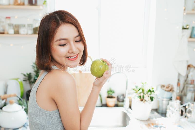 Счастливая молодая азиатская женщина есть зеленое Яблоко на кухне Диета умрите стоковое фото rf