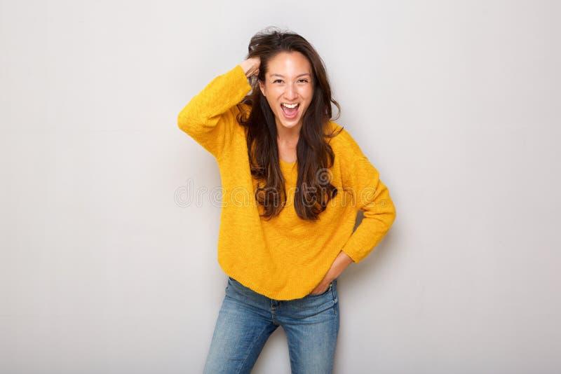 Счастливая молодая азиатская женщина смеясь с рукой в волосах против серой предпосылки стоковые фото
