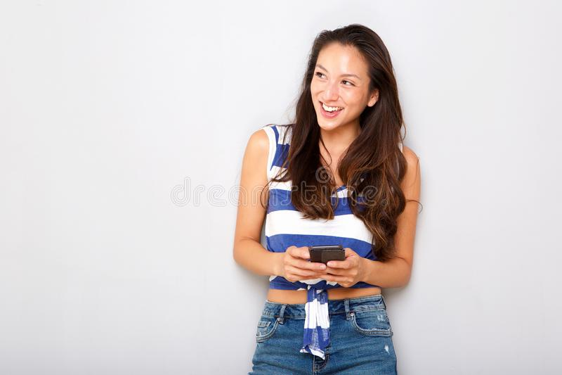 Счастливая молодая азиатская женщина с мобильным телефоном против серой предпосылки стоковое изображение