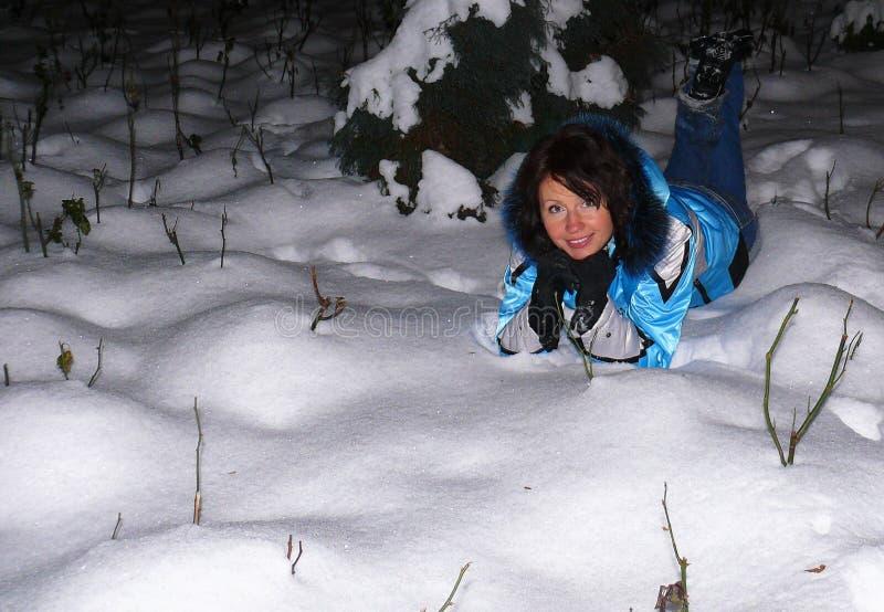 Счастливая молодая белая женщина лежит в снежном сугробе и улыбках, радостных эмоциях на стороне девушки стоковое фото rf