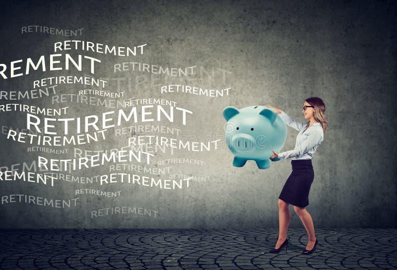 Счастливая молодая бизнес-леди привлекая пенсионные фонды по старости с копилкой магнита стоковая фотография rf