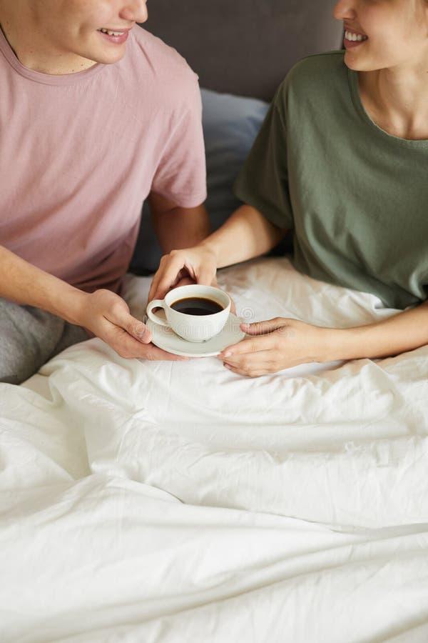 Счастливая молодая жена принимая чашку кофе от супруга стоковое фото rf
