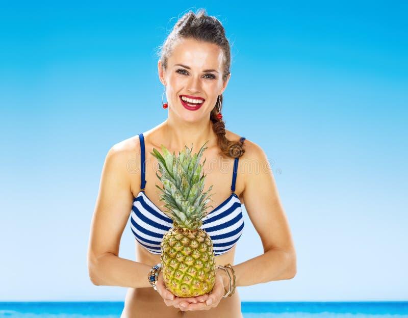Счастливая молодая женщина в купальнике на береге моря держа ананас стоковое фото rf