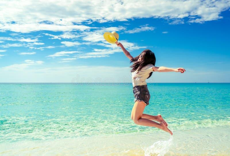 Счастливая молодая женщина в моде непринужденного стиля и соломенная шляпа скача на пляж песка Ослаблять, потеха, и насладиться п стоковая фотография