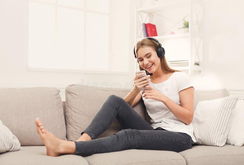 Счастливая молодая женщина в наушниках на бежевом кресле стоковые изображения rf