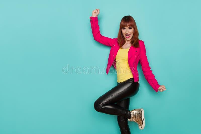 Счастливая молодая женщина в розовой куртке, черных кожаных брюках и тапках золота стоит на одной руке ноги, кричать и поднимать  стоковое фото