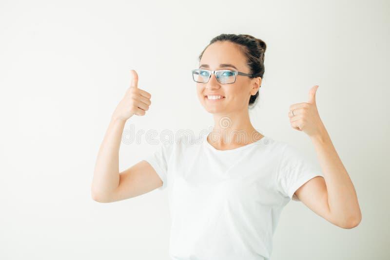 Счастливая молодая женщина давая большие пальцы руки вверх на белой предпосылке стоковое фото
