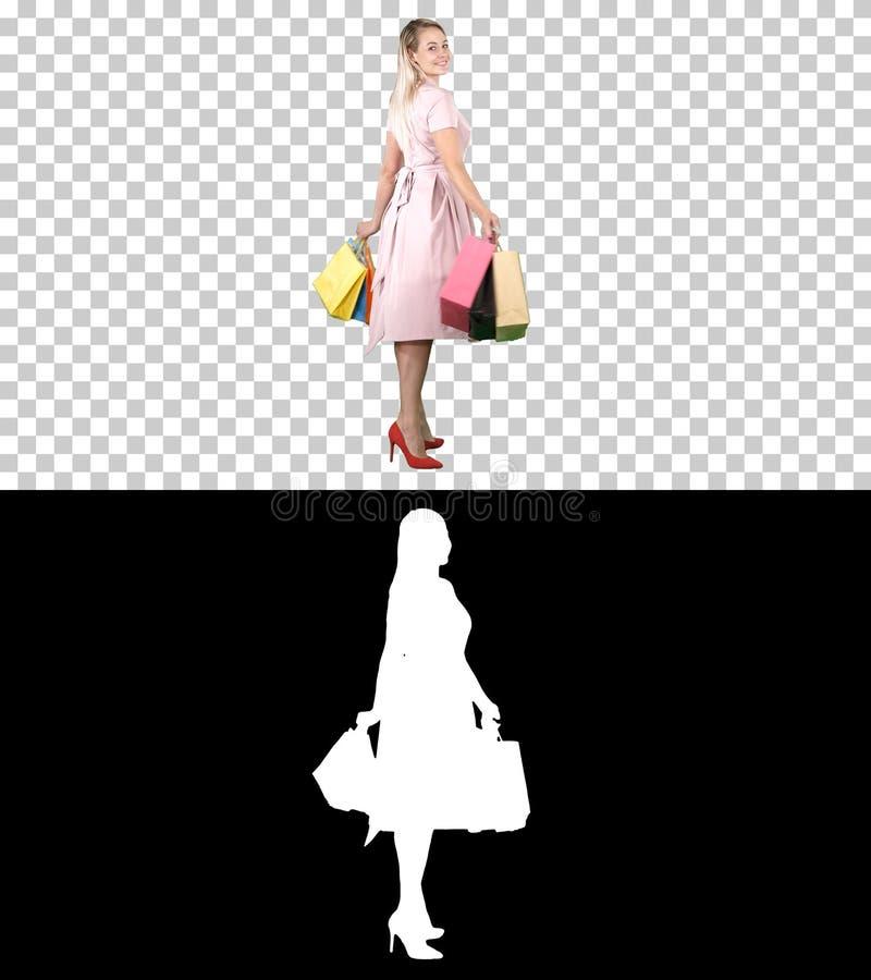 Счастливая молодая женщина делая поворот с хозяйственными сумками в ее руках смотря камеру, канал альфы стоковые изображения rf