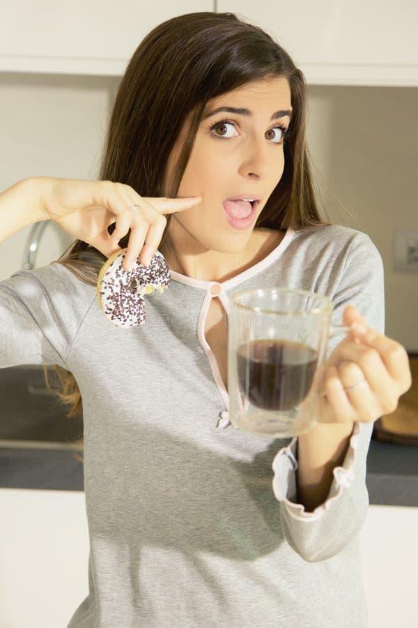Счастливая молодая женщина держа донут и кофе в кухне стоковое изображение rf