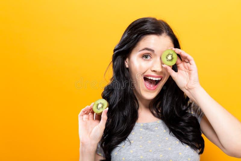 Счастливая молодая женщина держа кивиы стоковые фотографии rf