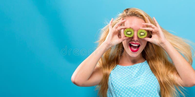 Счастливая молодая женщина держа кивиы стоковое фото rf