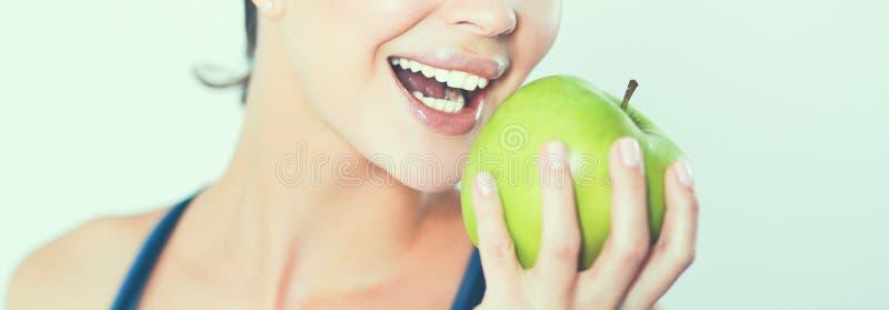 Счастливая молодая женщина есть яблоки, изолированные на белой предпосылке стоковые изображения