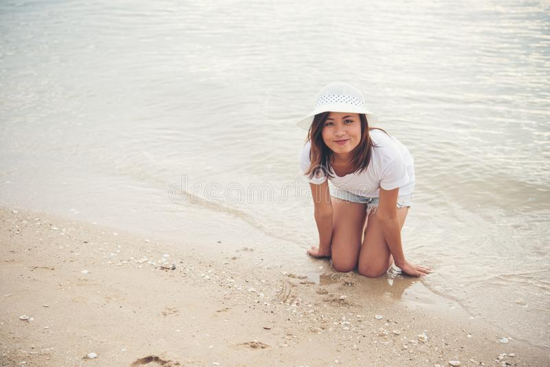 Счастливая молодая женщина играя на пляже на отпуске стоковые фотографии rf