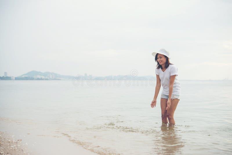 Счастливая молодая женщина играя на пляже на отпуске стоковое фото