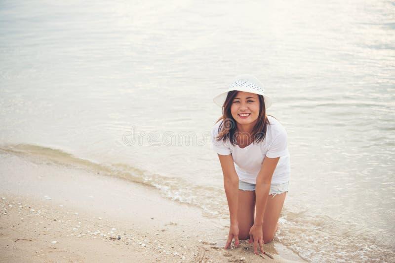 Счастливая молодая женщина играя на пляже на отпуске стоковая фотография