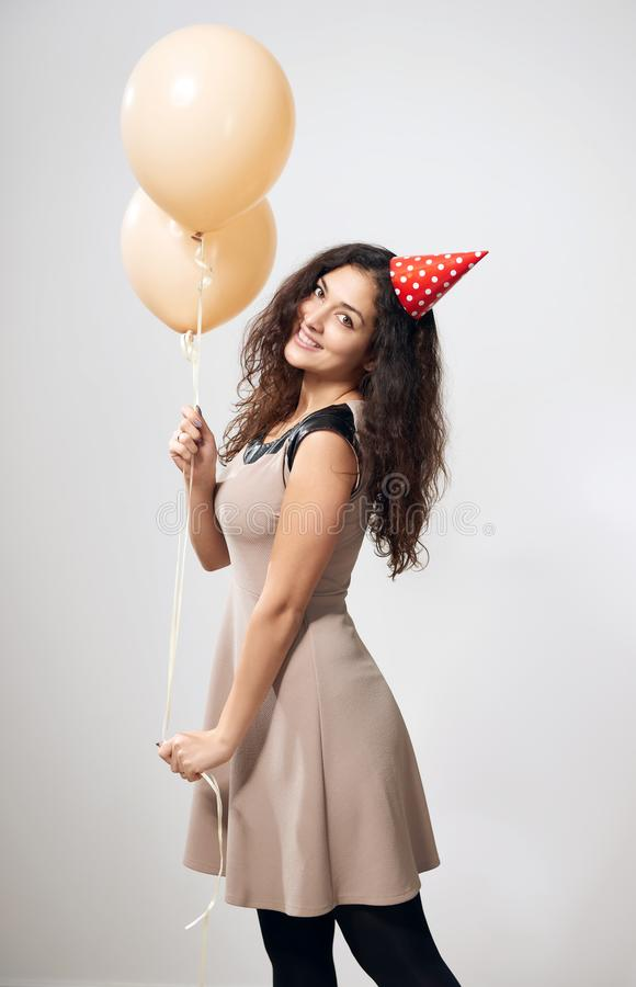 Счастливая молодая женщина или предназначенная для подростков девушка в коричневом платье с воздушными шарами гелия стоковое изображение rf
