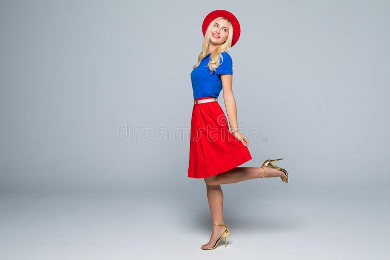 Счастливая молодая женщина или предназначенная для подростков девушка в одеждах и шляпе цвета имея потеху изолированные на серой  стоковое изображение rf