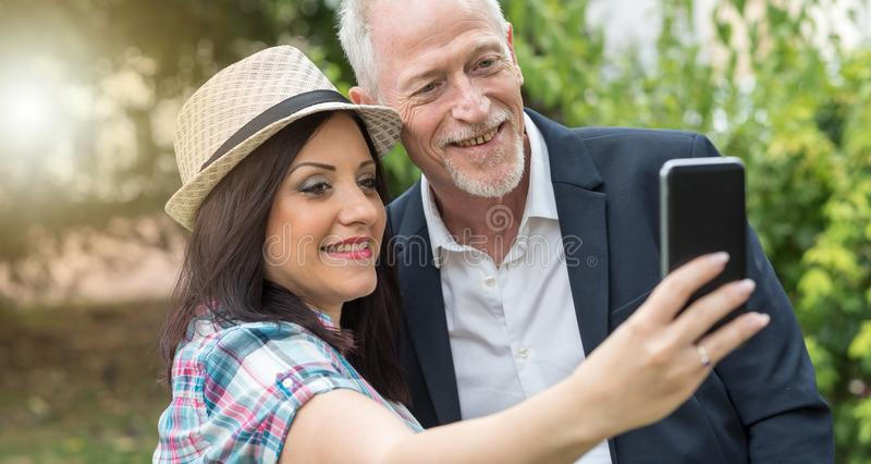 Счастливая молодая женщина и зрелый человек принимая selfie, световой эффект стоковые фотографии rf