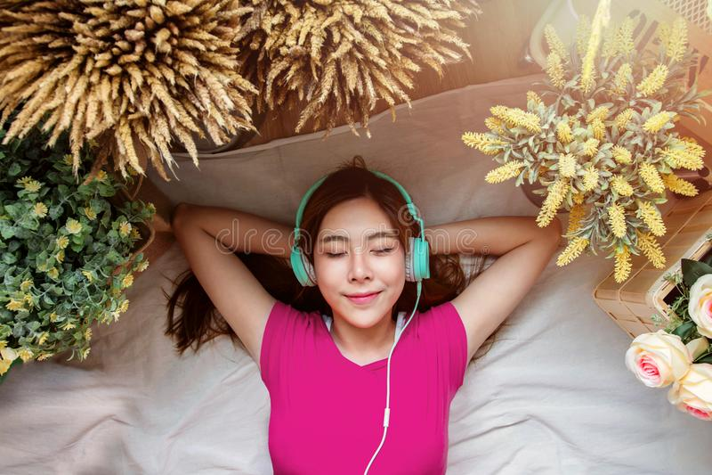 Счастливая молодая женщина кладя на пол к слушая музыке через Sma стоковая фотография rf