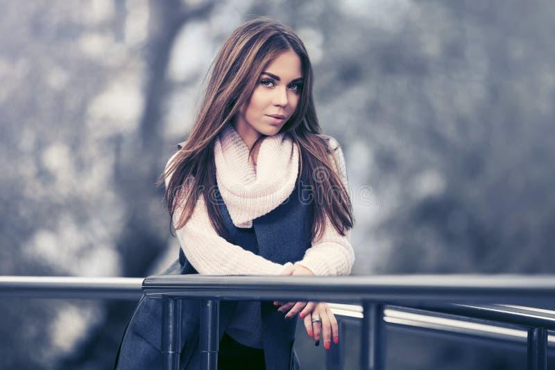Счастливая молодая женщина моды в безрукавном пальто полагаясь на перилах стоковое изображение rf