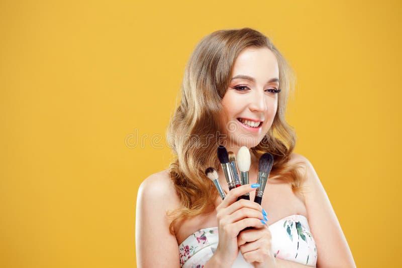 Счастливая молодая женщина наслаждается набором щеток макияжа Радостный визажист девушки стоковая фотография rf