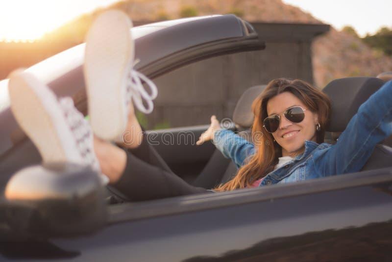 Счастливая молодая женщина наслаждаясь ее обратимым автомобилем стоковое изображение rf