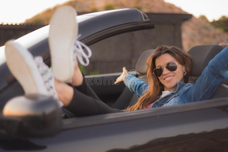 Счастливая молодая женщина наслаждаясь ее обратимым автомобилем стоковые фотографии rf