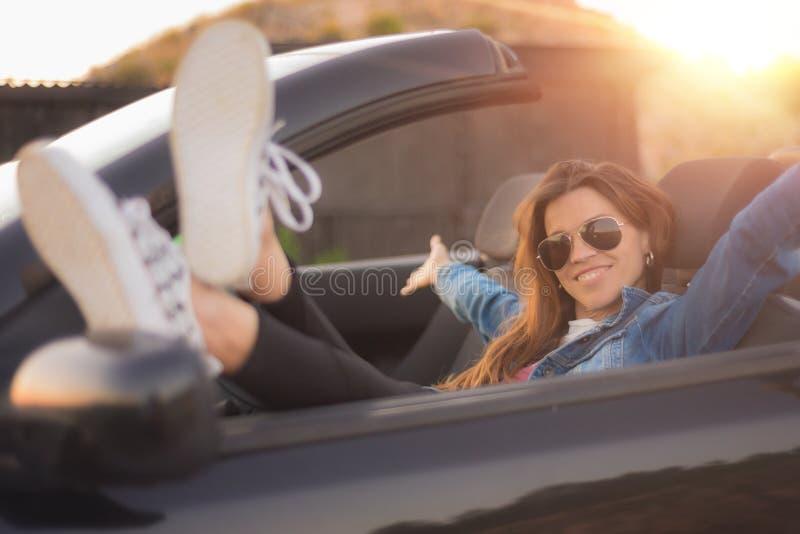 Счастливая молодая женщина наслаждаясь ее обратимым автомобилем стоковое изображение