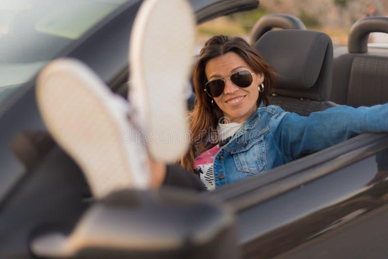 Счастливая молодая женщина наслаждаясь ее обратимым автомобилем стоковая фотография
