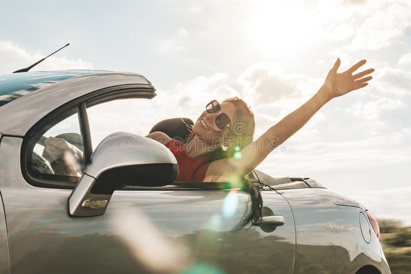 Счастливая молодая женщина наслаждаясь ездой в обратимом автомобиле приветствие руки концепция перемещения и приключения дороги е стоковые фотографии rf